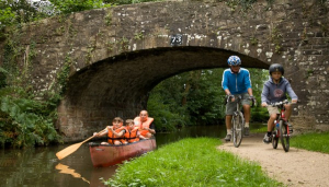 People canoeing on canal and cycling on towpath
