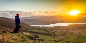 Sunset over Llangorse lake with man and dog on Mynydd Llangorse