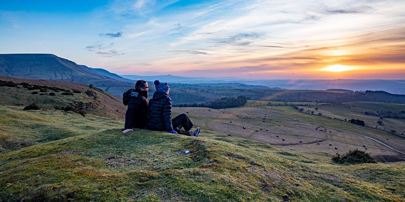 Couple sit at base of Hay Bluff looking out at the sunset